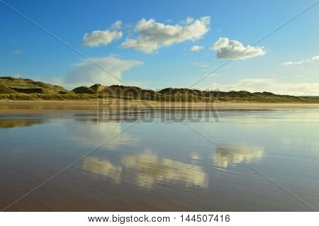 Cloud reflections on Freshwater west beach Pembrokeshire. Captured on a bright and sunny day with clear blue sky.