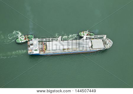 Tugboats moving a large cargo ship into place at the mouth of a large harbor