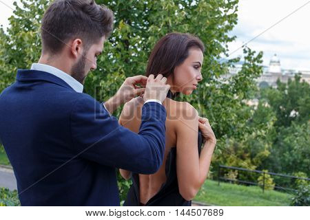 Elegant stylish man help dressing woman outdoor