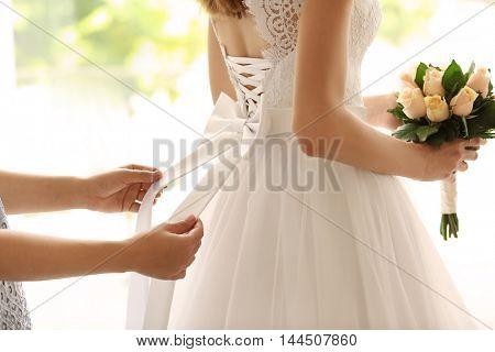 Bridesmaid tying bow on wedding dress