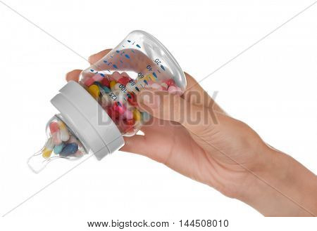 Woman hand holding feeding bottle full of pills on white background