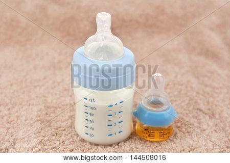 Feeding bottle with baby milk formula and bottle with medicine on towel background