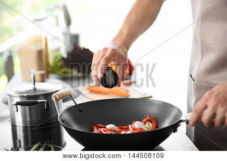 Male hand adding salt to vegetables in pan closeup