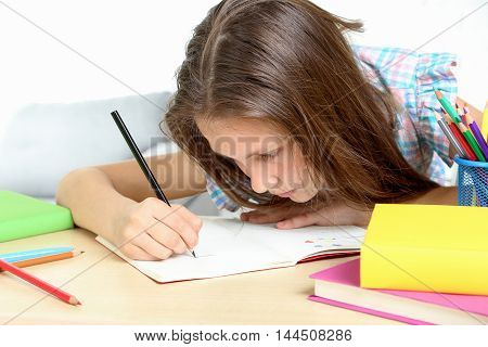 Young Girl Sitting At The Desk And Drawing