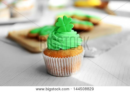 Tasty cupcake with clover on table. Saint Patrics Day concept