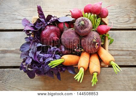 Crate with fresh vegetables on wooden background