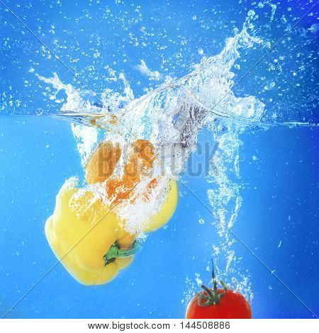 Group of fresh fruits and vegetables falling in water on blue background