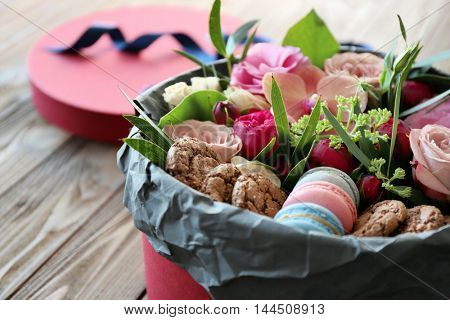 Box with fresh flowers and macaroons on wooden background