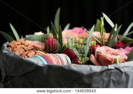 Box with fresh flowers and macaroons, closeup