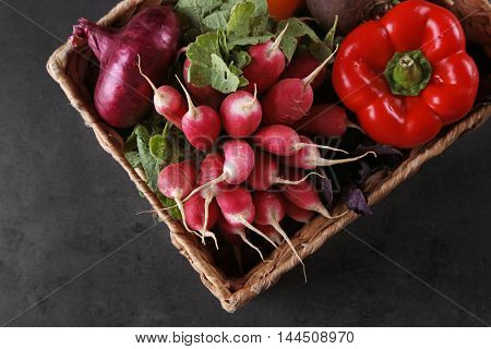 Fresh vegetables in wicker basket on dark background, top view