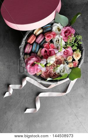 Box with fresh flowers and macaroons on grey background, top view