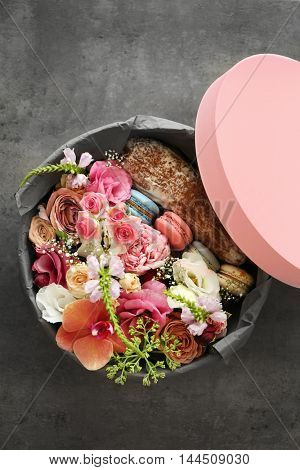 Gift box with flowers and cookies on dark background