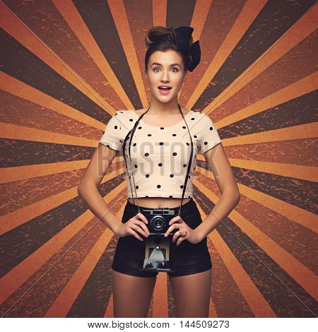 Beautiful young woman with retro photo camera. Surprised expression. Retro style texturized background.