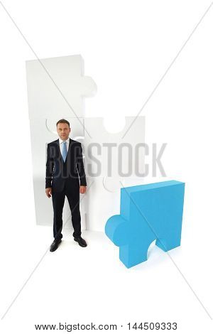 Portrait of business man and puzzle isolated on white background