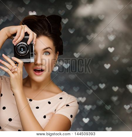 Beautiful young woman with retro photo camera. Surprised expression. Closeup portrait.  Over heart shape bokeh background. Copy space. Square composition.