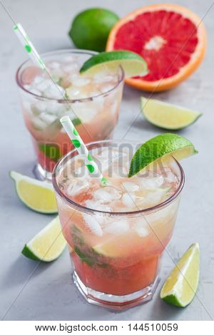 Cold pink cocktail with fresh grapefruit lime and ice cubes on concrete background paloma