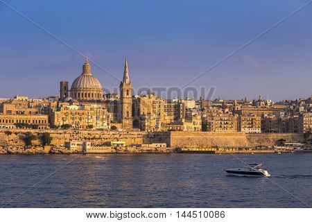 Valletta Malta - Motorboat and the famous St.Paul's Cathedral with the ancient city of Valletta at sunset