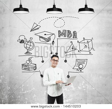 Asian man with laptop standing near concrete wall with MBA sketch on it. Concept of business education