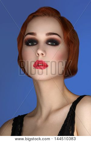 Beautiful young woman with smoky eyes and full red lips. Studio beauty shot over blue background. Copy space.