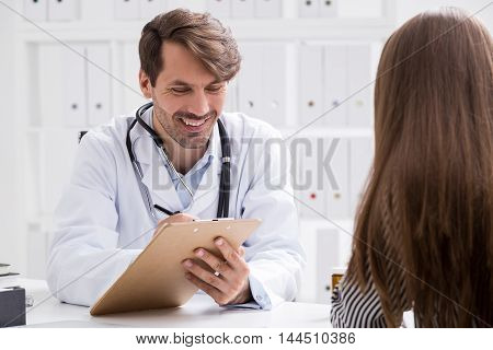 Smiling doctor taking notes. Patient explains her symptoms. Treatment going well. Concept of healthy patient