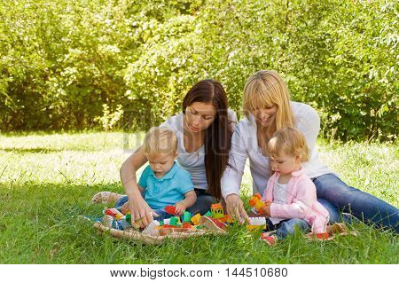 parents playing with children with construction blocks. Early child development