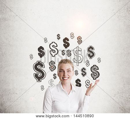 Smiling girl in white shirt pointing upwards and standing near concrete wall with dollar sign sketches. Concept of business coaching. Mockup