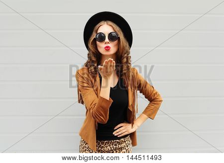 Fashion Lifestyle Portrait Woman Sends Air Sweet Kiss Wearing A Black Hat, Sunglasses And Brown Jack