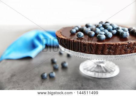 Delicious chocolate tart with blueberry on grey table
