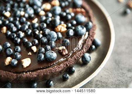 Delicious chocolate tart with blueberry and nuts on plate, closeup