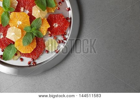 Plate with different citrus slices on grey background