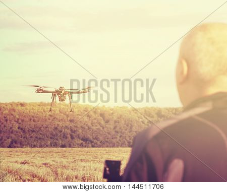 Silhouette Of A Man Operating A Drone With Remote Control For Video Shooting In A Summer Day. Sun Fi