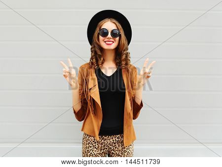 Fashion Pretty Smiling Woman Wearing A Black Hat, Sunglasses And Jacket Over Urban Grey Background