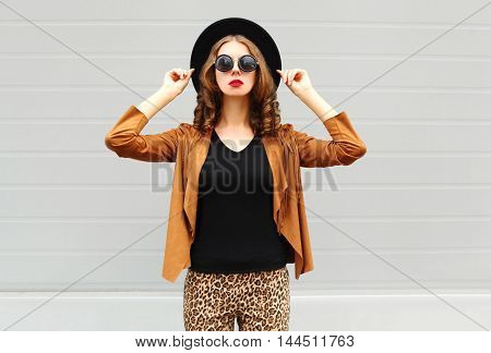 Fashion Pretty Woman Wearing A Black Hat, Sunglasses And Jacket Over Urban Grey Background