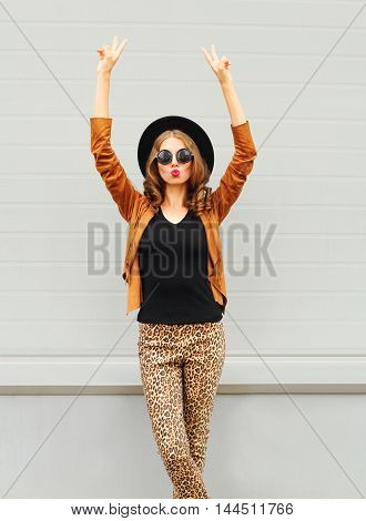 Fashion Pretty Young Woman Wearing A Black Hat, Sunglasses And Jacket Raises Hands Up Over Urban Gre