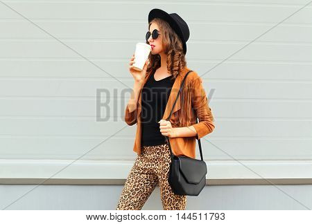 Fashion Pretty Young Woman Drinks Coffee Of Cup Wearing A Retro Elegant Hat, Sunglasses, Brown Jacke