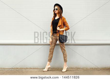 Fashion Pretty Young Woman Wearing A Retro Elegant Hat, Sunglasses, Brown Jacket And Black Handbag W