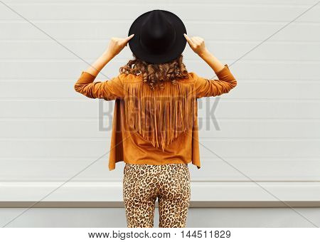 Fashion Woman View From Back Wearing A Black Hat, Sunglasses And Jacket Over Urban Grey Background