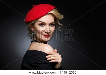 Beautiful lady in red beret. Beauty portrait. Red lips. Over black background. Copy space.