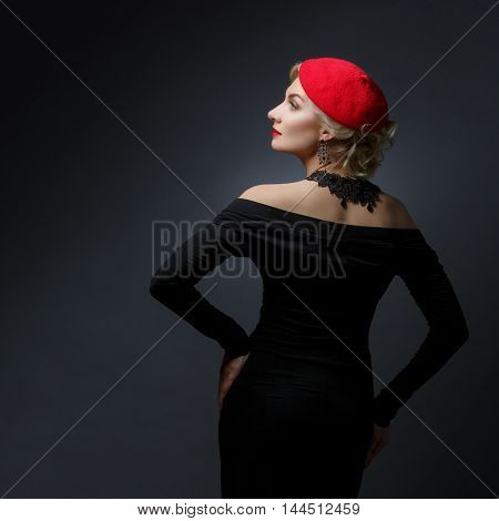 Back of beautiful lady in red beret standing over black background. Copy space. Studio shot.