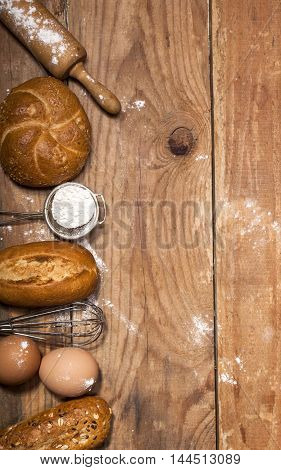Ingredients and utensils for the preparation of bakery products - flour, eggs, rolling pin, whisk, strainer, bread - on rustic wooden table with free copy space