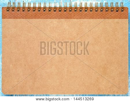 Brown notebook paper on blue wooden floor.