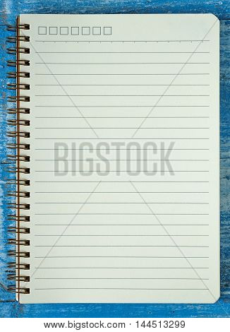 White notebook paper on blue wooden floor.