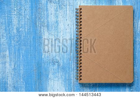 Brown notebook on a blue wooden floor.