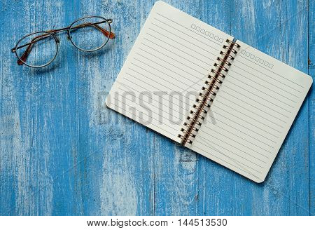 White notebook with glasses on blue wooden floor.