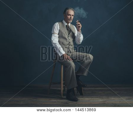 Cigar Smoking Retro 1920S Man Wearing Suit Sitting On Wooden Stool. Empty Room. Vintage Wooden Floor