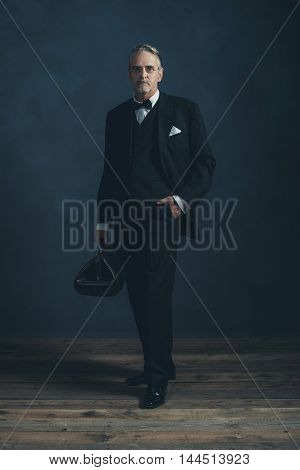 Retro 1920S Doctor In Black Suit With Bow Tie. Holding Handbag.
