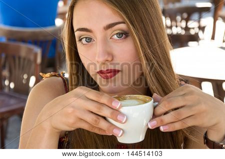 beautiful woman holding a cup of delicious hot coffee