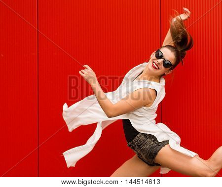 Stylish woman dancing and jumping on a street agains a red wall