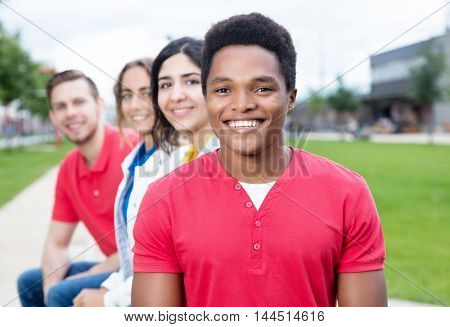 Cheerful african american guy and multiethnic friends outdoor in the summer