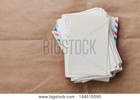 Stack of old envelopes and letters on kraft paper. Top view.